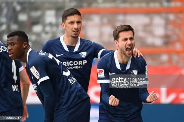 Bochum's Serbian forward Milos Pantovic celebrates after scoring with Bochum's Austrian midfielder Robert Zulj and Bochum's German defender Armel...