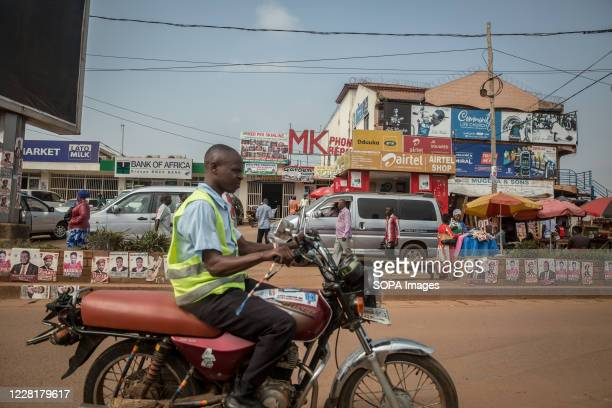 Boda boda rider passes election posters along the road in Kampala. Uganda's elections are expected to take place early next year.
