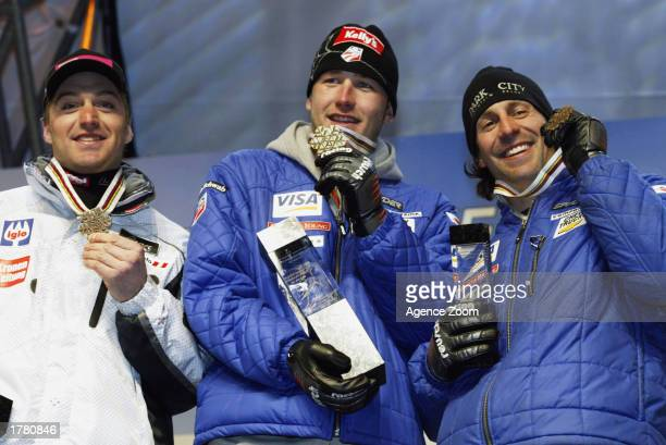 Bode Miller of the USA Gold Medal Hans Knauss of Austria Silver Medal and Erik Schlopy of the USA Bronze Medal celebrate on the podium after the...