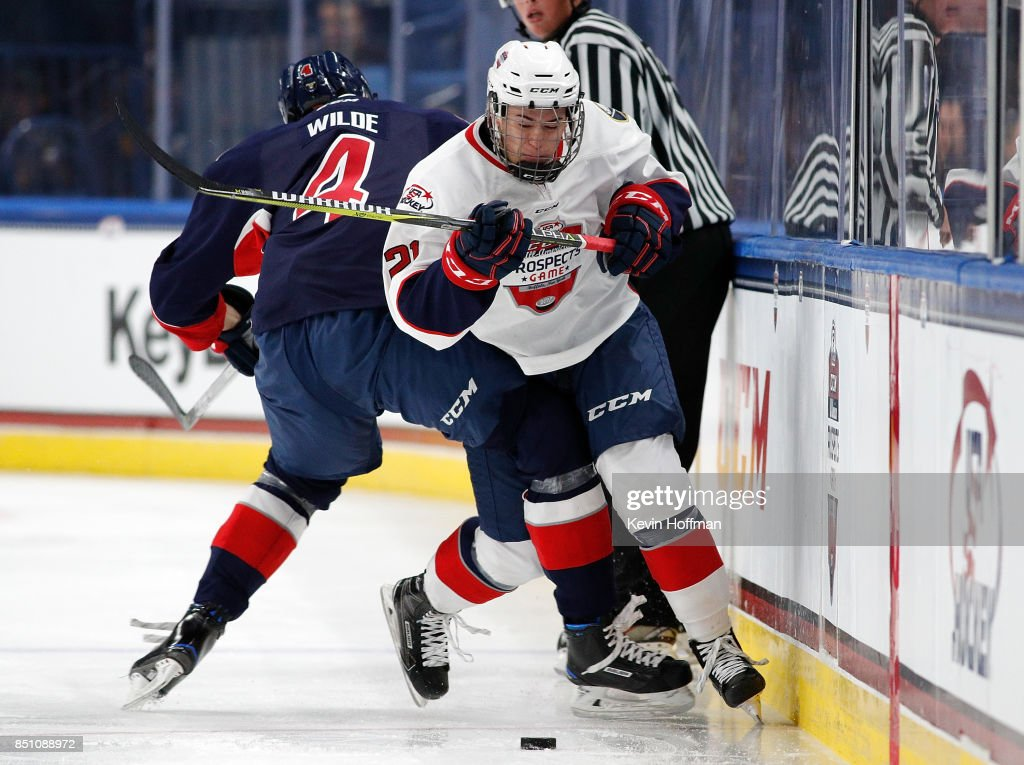 Bode Wilde #4 of Team Leetch checks Jay O'Brien #21 of Team Chelios in the third period during the CCM/USA Hockey All-American Prospects Game at the KeyBank Center on September 21, 2017 in Buffalo, New York. Team Leetch beat Team Chelios 6-5.
