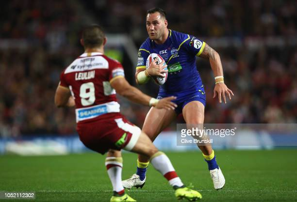 Bodene Thompson of the Warrington Wolves is confronted by Tommy Leuluai of the Wigan Warriors during the BetFred Super League Grand Final between...