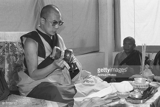 The Dalai Lama plays a small drum while praying before delivering the Kalchakra sermon on the spot in Bodh Gaya where some Buddhists say the Lord...