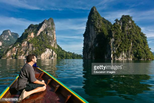 Bodhi Garrett admires the KARST FORMATIONS rising out of CHEOW LAN LAKE in KHAO SOK NATIONAL PARK THAILAND