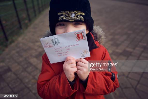 Bodie Cattermole, the photographer's son, posts a letter to Santa via Royal Mail on December 06, 2020 in Essex, England. Writing letters to Santa...