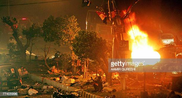 Bodies and injured lie on a road as fire erupts from a car in front of a vehicle carrying of former Pakistani prime minister Benazir Bhutto after...