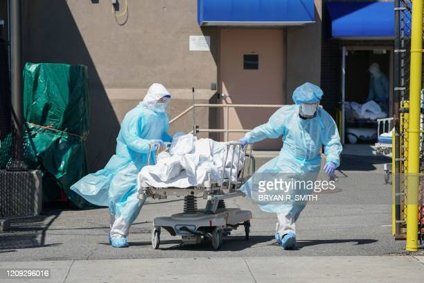 TOPSHOT Bodies are moved to a refrigeration truck serving as a temporary morgue at Wyckoff Hospital in the Borough of Brooklyn on April 6 2020 in New...