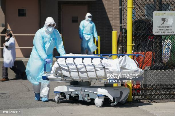 Bodies are moved to a refrigeration truck serving as a temporary morgue at Wyckoff Hospital in the Borough of Brooklyn on April 6 2020 in New York...