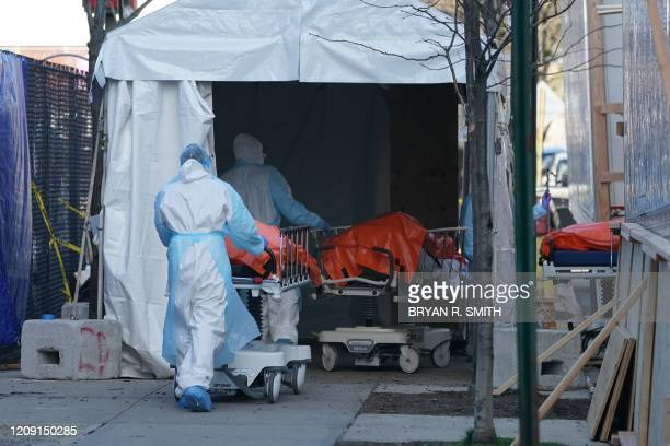Bodies are moved to a refrigerator truck serving as a temporary morgue outside of Wyckoff Hospital in the Borough of Brooklyn on April 4, 2020 in New...
