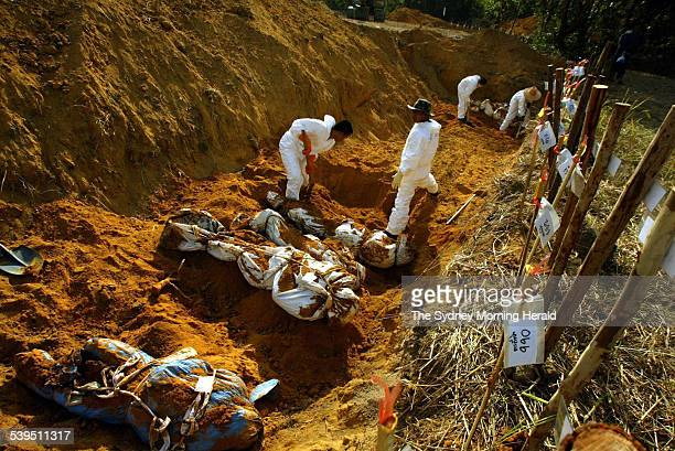 Bodies being dug up at the mass grave in Bang Maruen village in Thailand before being transported back to the morgue to undergo thorough...