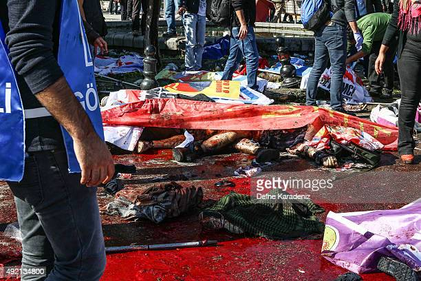 Bodies lay covered with flags and banners at the blast scene after an explosion during a peace march in Ankara October 10 2015 in Ankara Turkey At...