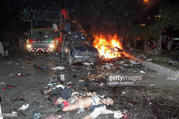 Bodies lie on a road as fire erupts from a car in front of a vehicle carrying of former Pakistani prime minister Benazir Bhutto after bomb explosion...