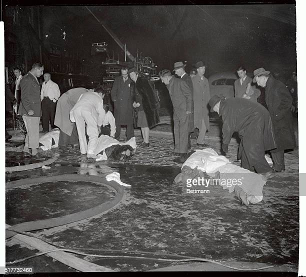 Bodies of four victims of the fire that destroyed Boston's popular Cocoanut Grove Night Club last night lie in the street waiting removal to the...
