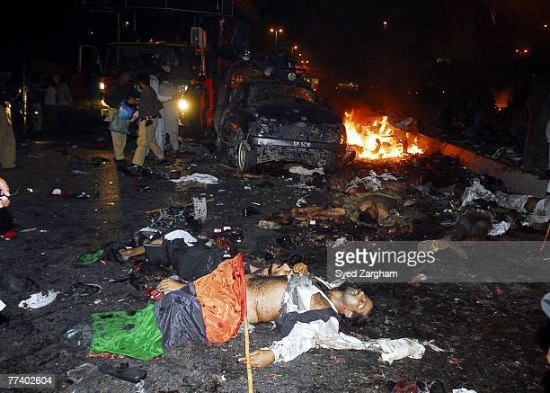Bodies of Pakistani people party activists lay in the street after a powerful suicide car bomb blast was set off near a vehicle carrying former...