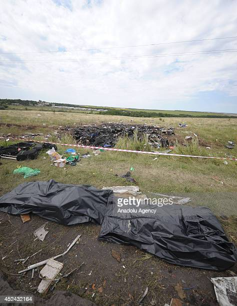 Bodies of passengers in body bags are seen near the security cordon of crash site as representative from monitoring group of Organization for...