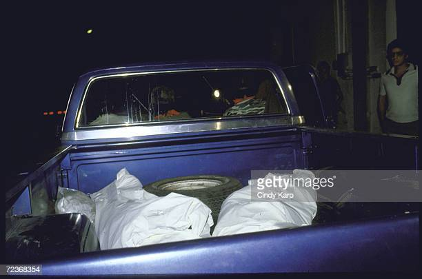 Bodies of slain DEA agent Enrique Camarena Salazar and pilot Alfredo Zavala Avelar covered with sheets lying in back of pickus truck near Guadalajara