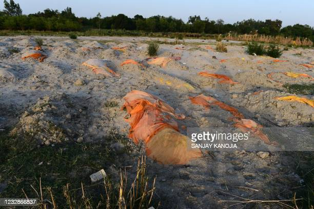 Bodies of suspected Covid-19 coronavirus victims are seen in shallow graves buried in the sand near a cremation ground on the banks of Ganges River...