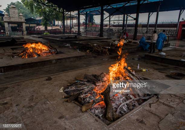 Bodies of the victims who died of the coronavirus disease , burn on funeral pyre at a crematorium, on July 21, 2020 in New Delhi, India. Spike of...