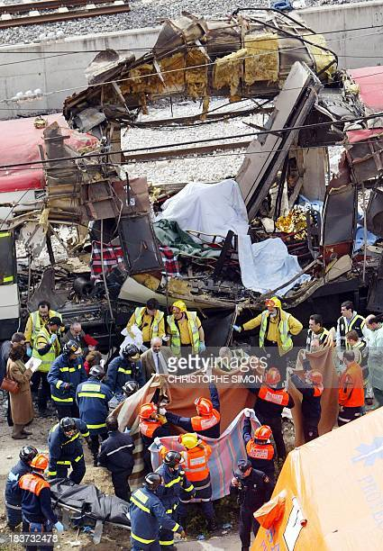 Bodies of victims are evacuated after a train exploded near the Atocha train station in Madrid 11 March 2004 At least 131 people were killed and some...