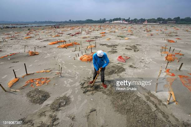Bodies, some of which are believed to be Covid-19 victims, are seen partially exposed in shallow sand graves after rains washed away the top layer of...