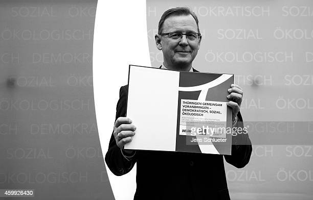 Bodo Ramelow head of the Die Linke party faction in the Thuringia state parliament poses for a photo after the signing the coalition contract between...