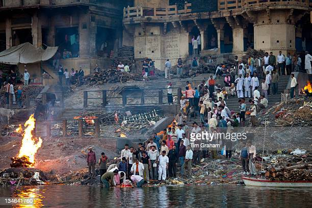 Body bathed in River Ganges and traditional Hindu cremation on funeral pyre at Manikarnika Ghat in Holy City of Varanasi Benares India