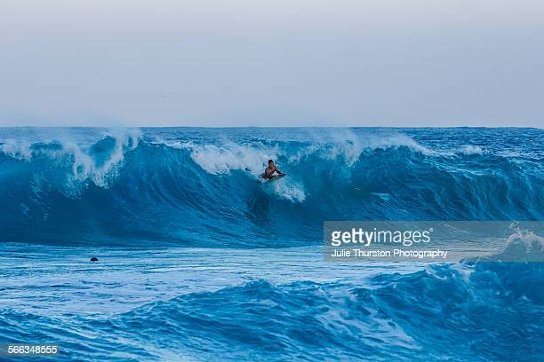 Body boarder on boogie board enjoys riding teal waves on a sunny blue sky day in Kailua Hawaii on the Island of Oahu Beautiful Kaneohe Bay and...