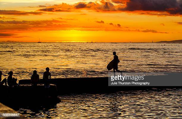 Body boarder walks along a wall against an orange glowing sunset with surfers riding waves in the distance at the tourist travel destination surfing...