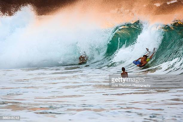 Body boogie boarders riding the waves at sunset at the travel vacation destination Waimea Bay Beach Park on the North Shore of Hawaii on the Island...
