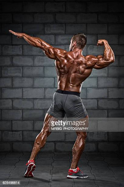 body builder flexing muscles - handsome bodybuilders stock photos and pictures