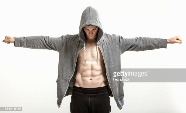 body builder in hoodie with outstretched arms exposing abdominal muscle - heshphoto stock pictures, royalty-free photos & images
