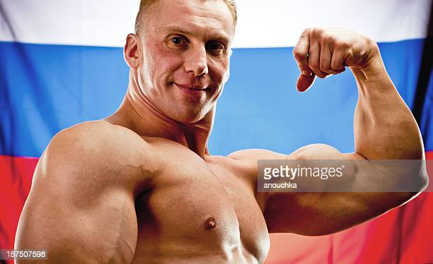 Body Builder Posing with Russian flag on background