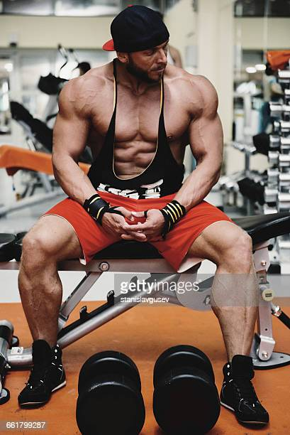 body builder sitting on bench in gym - bodybuilding stock-fotos und bilder
