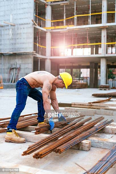 Body builder working on construction site with steel rods