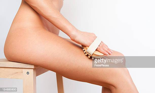 Body care at home. Cellulite massage with natural wooden brush