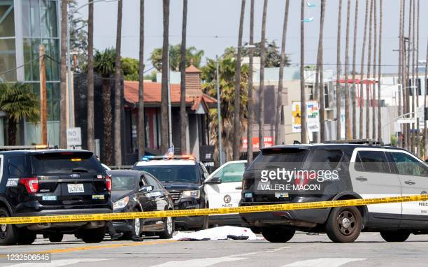 Body covered in a white sheet lies next to a black vehicle covered with stickers and a shattered driver side window, as police cars block traffic at...
