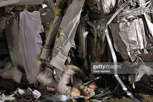 A body falls from the wreckage of a Metrolink commuter train that collided headon with a freight train the previous afternoon on September 13 2008 in...