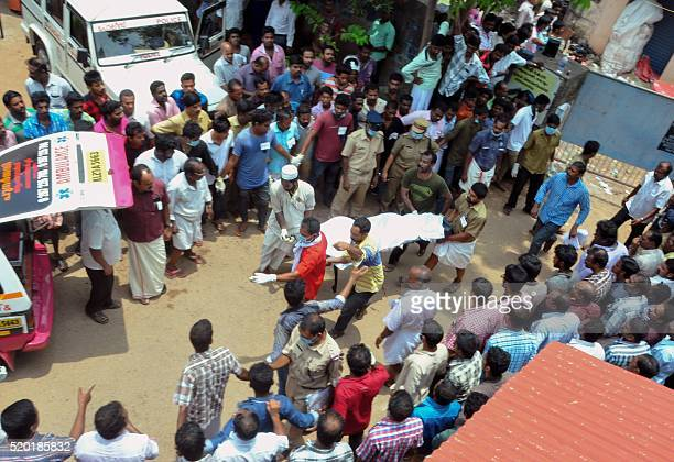 A body is carried to an ambulance following a huge fire in Paravur at the Puttingal Devi Temple in the southern Indian state of Kerala on April 10...