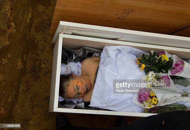 A body is covered with flowers at a temporary burial ground on March 25 2011 in Higashimatsushima Miyagi Japan Under Japanese Buddhist practice a...