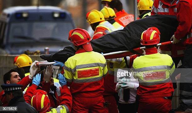 Body is lifted from the wreckage of a commuter train March 11, 2004 after it was devastated by a bomb blast during the morning rush hour in Madrid,...