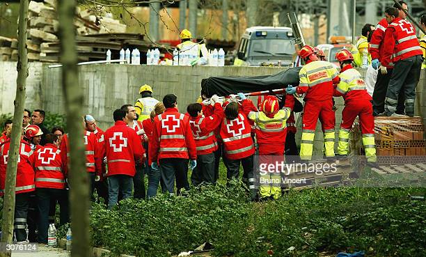 A body is lifted from the wreckage of a commuter train March 11 2004 after it was devastated by a bomb blast during the morning rush hour in Madrid...