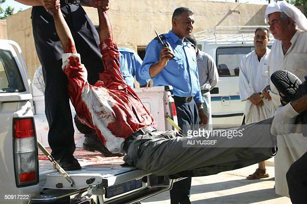 A body is lifted out from the back of a pickup truck following a shooting in the town of Baquba 60 kms northeast of Baghdad 02 June 2004 Four people...