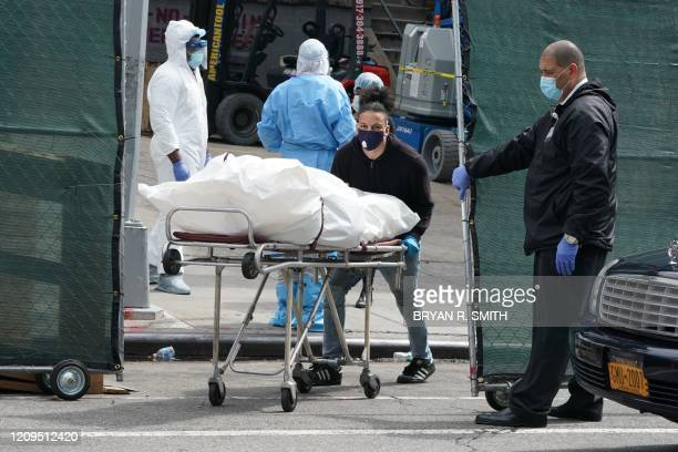 Body is moved from a refrigeration truck serving as a temporary morgue to a vehicle at the Brooklyn Hospital Center, in the Borough of Brooklyn on...