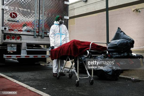 A body is moved on the street outside the Andrew Cleckley Funeral Home on April 30 2020 in the Brooklyn borough of New York City Dozens of bodies...