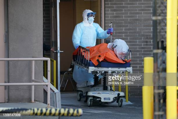 A body is moved to a refrigerator truck serving as a temporary morgue outside of Wyckoff Hospital in the Borough of Brooklyn on April 4 2020 in New...