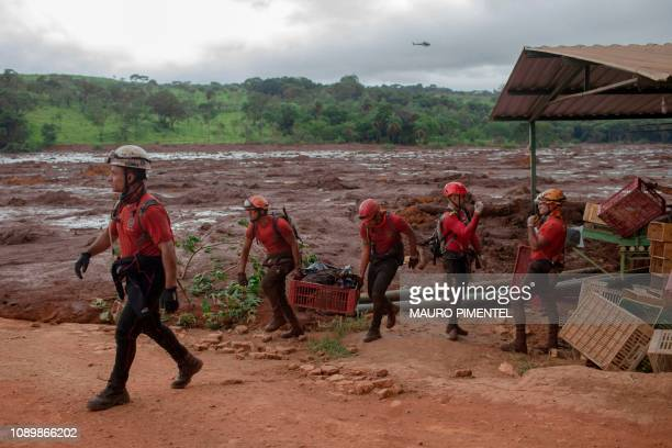 A body is recovered by Minas Gerais firefighters from a small market at the mudhit area a day after the collapse of a dam at an ironore mine...