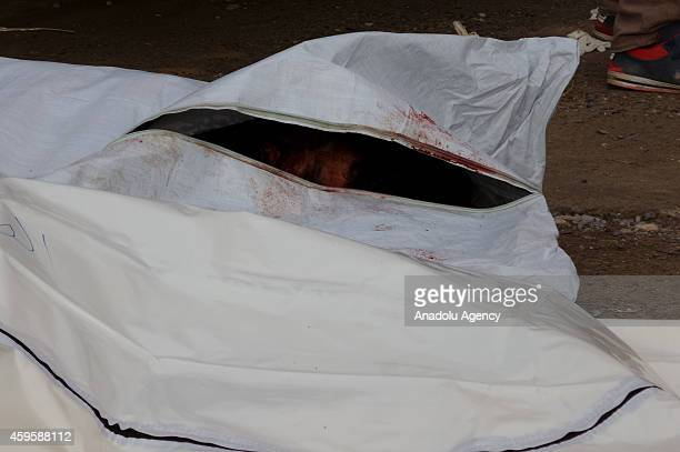 A body is seen in a body bag after the air strikes by Syrian army warplanes on the ISILheld northern city of Raqqa Syria on November 25 2014 At least...
