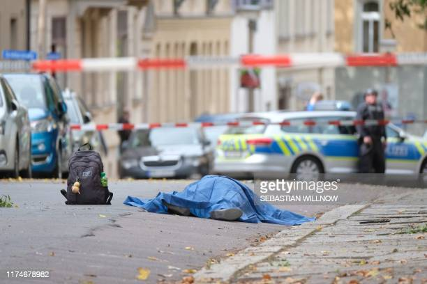 TOPSHOT A body laying in the street is covered as police block the area around the site of a shooting in Halle an der Saale eastern Germany on...