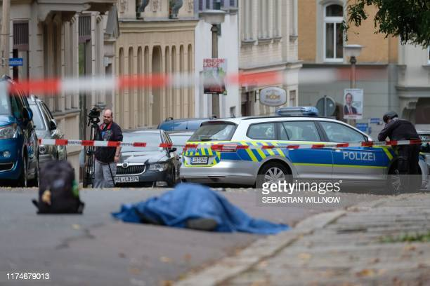 A body laying in the street is covered as police block the area around the site of a shooting in Halle an der Saale eastern Germany on October 9 2019...