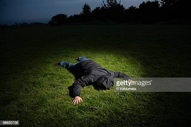 body laying on grass - dead body foto e immagini stock