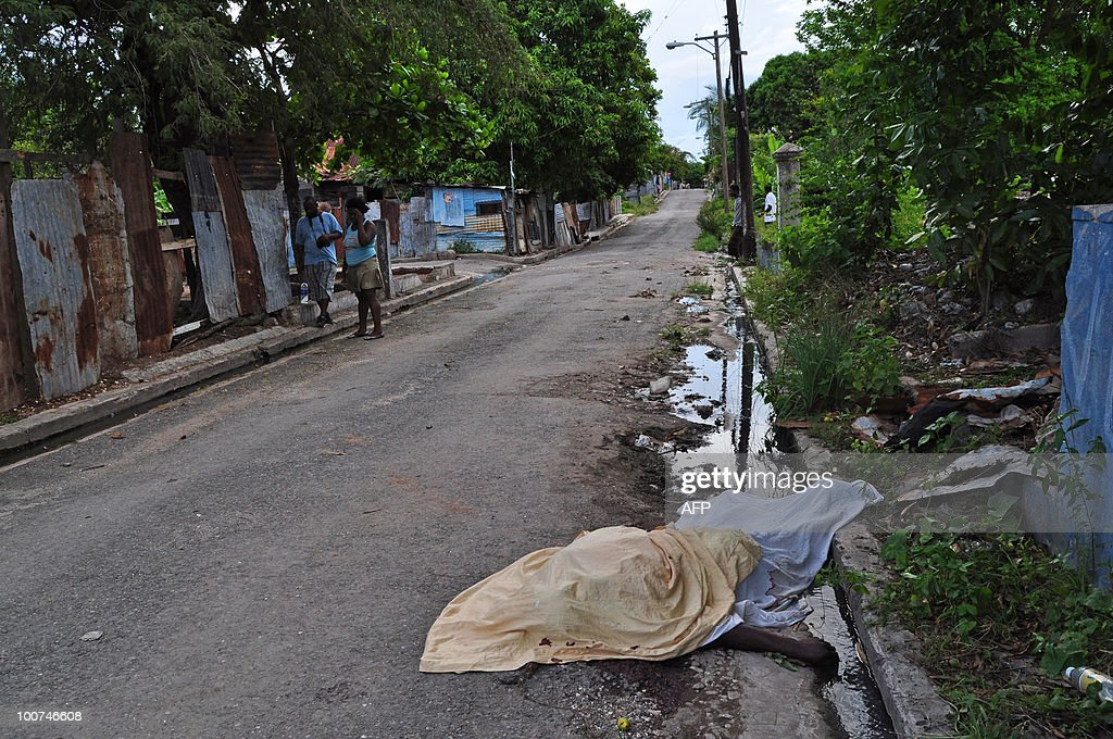A body lies covered up in sheets in a street in the Trench Town neighborhood of Kingston, Jamaica on May 24, 2010 following clashes. The body wasn't taken to the local morgue because no ambulance accepts to go into West Kingston. Gun battles raging in the Jamaican capital have left more than 60 people dead, mostly civilians, hospital sources said May 25, as troops fanned out across the city hunting an alleged drug kingpin. Hundreds of troops and police have been deployed to hunt down Christopher 'Dudus' Coke, wanted in the United States on drug-trafficking charges, amid a week-long standoff with his loyal supporters. AFP PHOTO / Ratiba HAMZAOUI